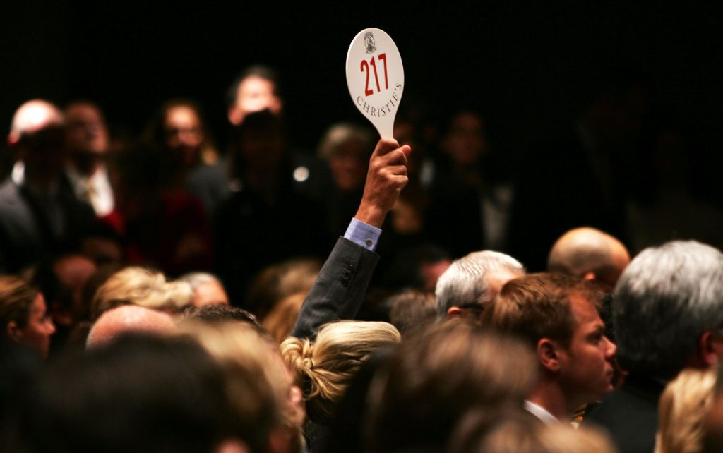 A man holds up a paddle at an auction.