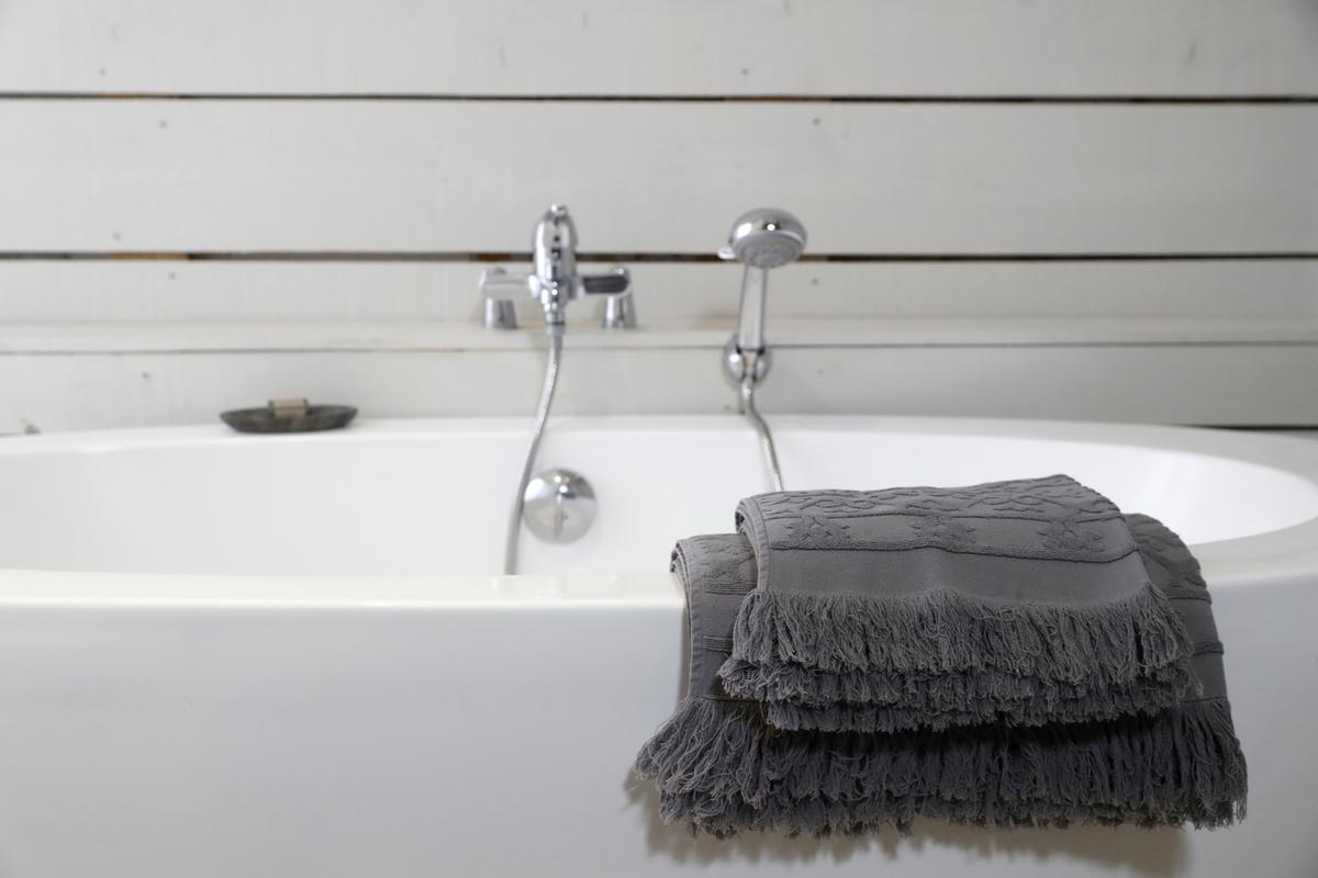 Grey bath towels are draped over a ceramic tub.