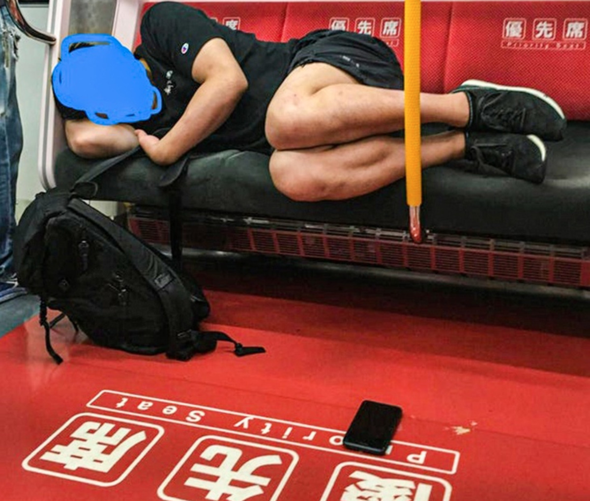 person sleeps on commuter train with phone on floor