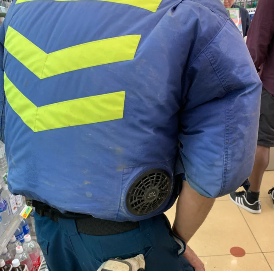 construction worker with puffy jacked with fan in back