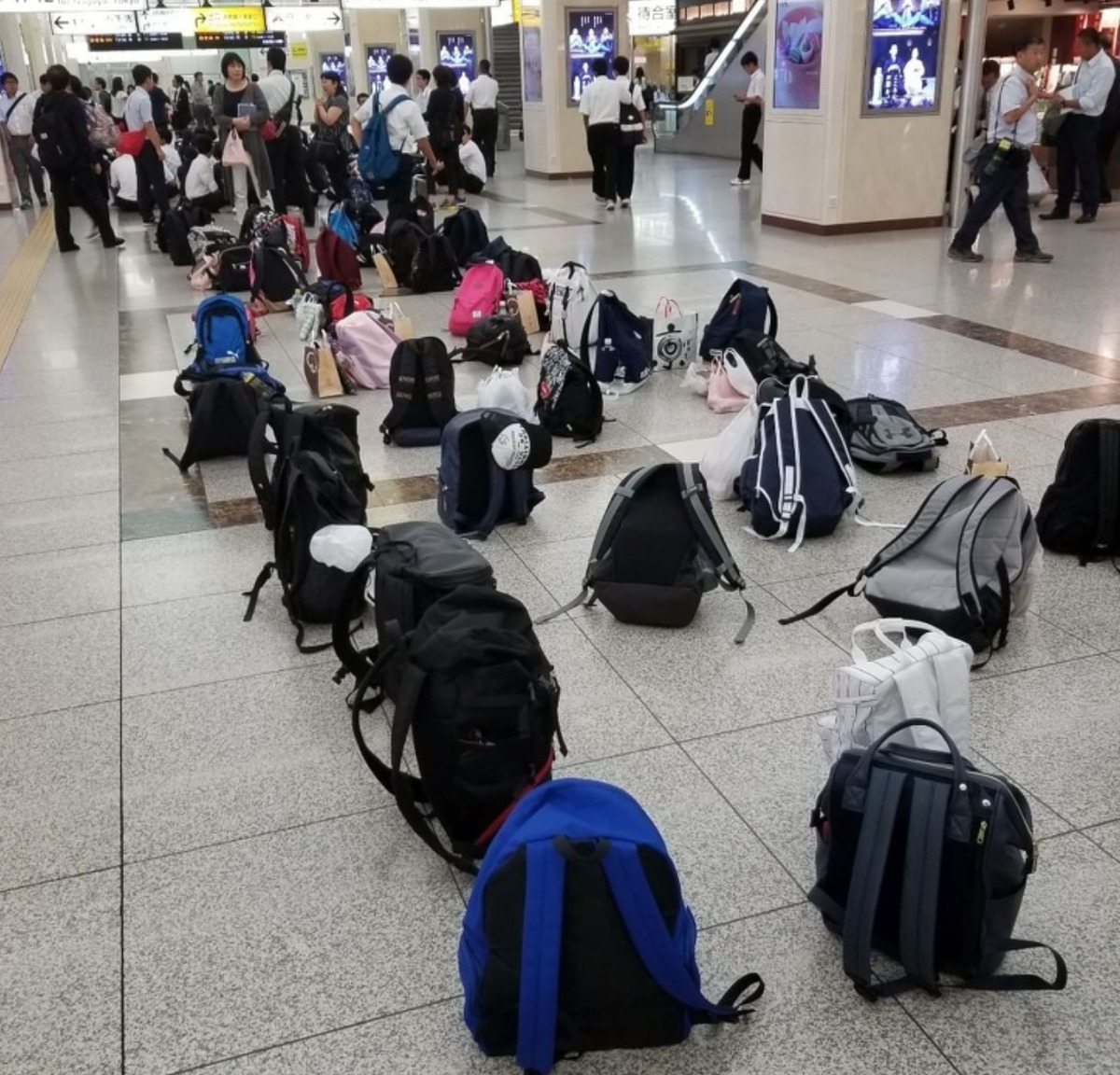 collection of backpacks on the ground at train station