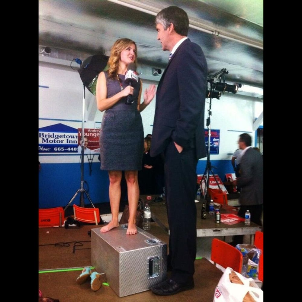 Reporter stands on box to speak with man
