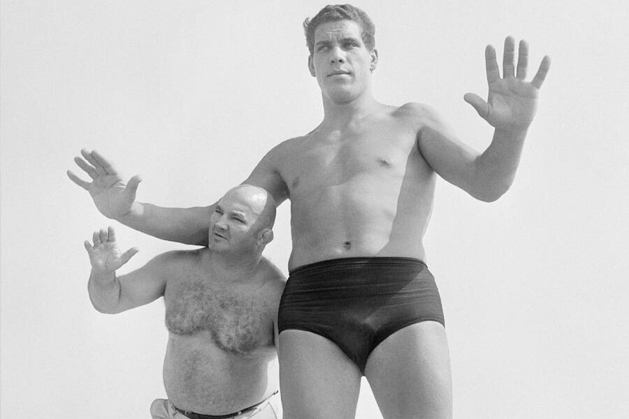 aandre the giant standing next to normal size man