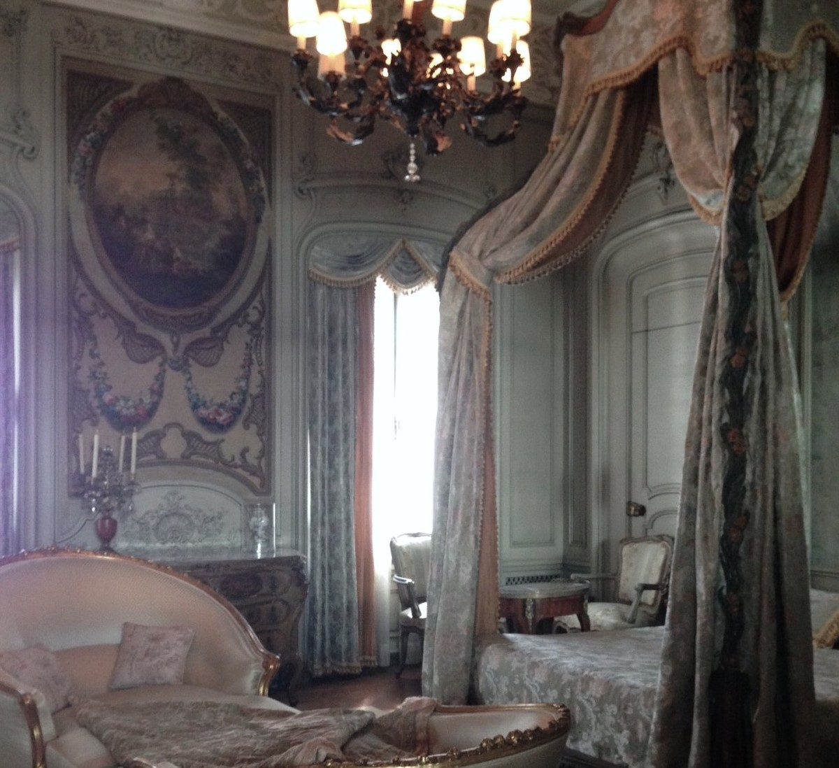 A large bedroom is exemplified by luxurious decor.
