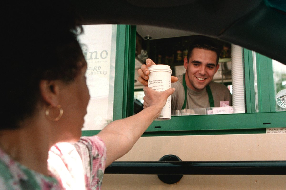 Starbucks Coffee employee delivers a coffee order to a customer through a window of a drive-up Starbucks shop.