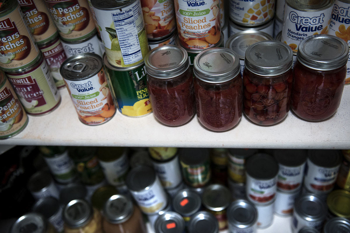 Canned food including fruit preserves is seen in a pantry.