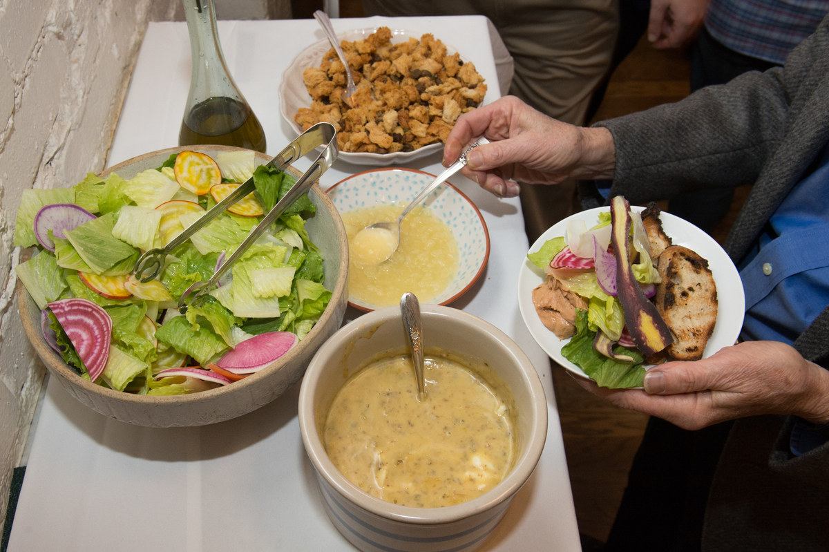 A person adds salad dressing to their meal.