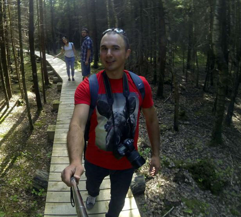 Erikas takes a photo in the forest with a selfie stick.