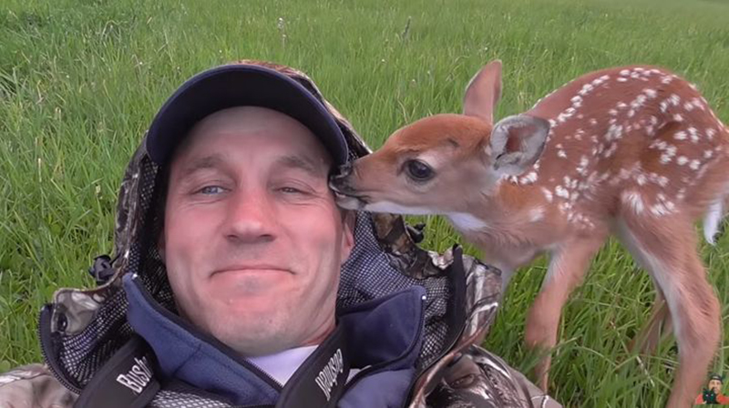 A baby deer nuzzled a man's face.