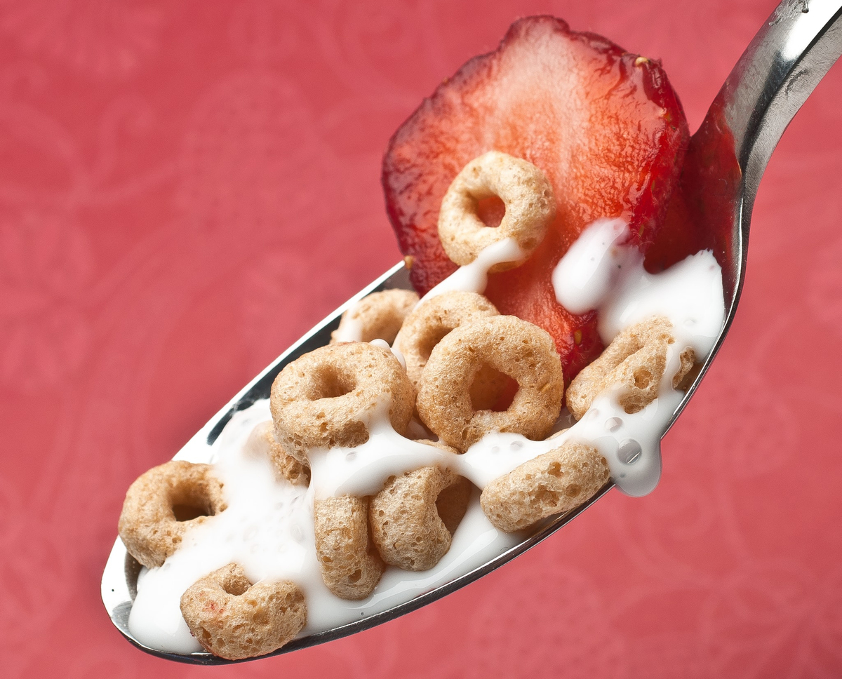 A spoon carries milk, Cheerios cereal, and a strawberry slice.