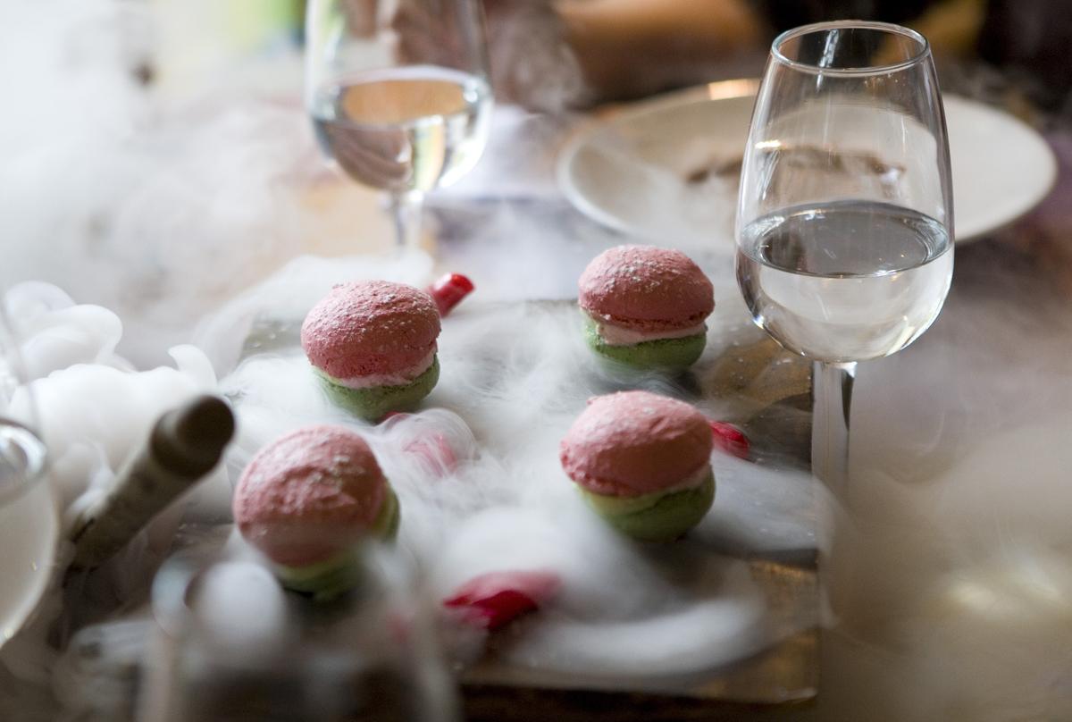 Liquid nitrogen smoke swirls around a dessert.