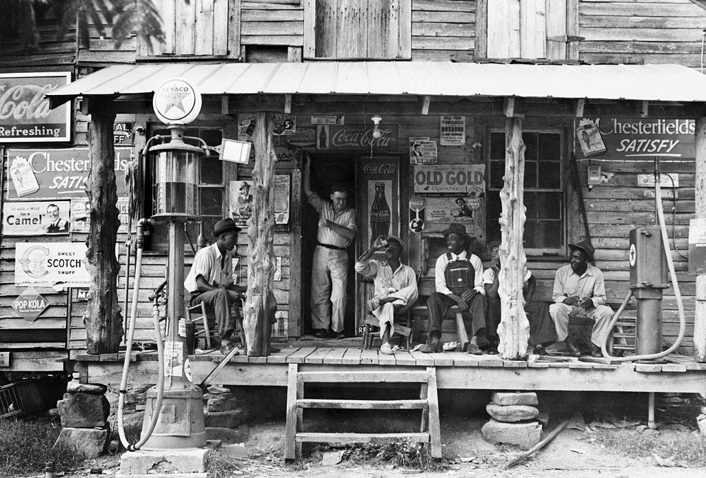 Men sitting in front of store