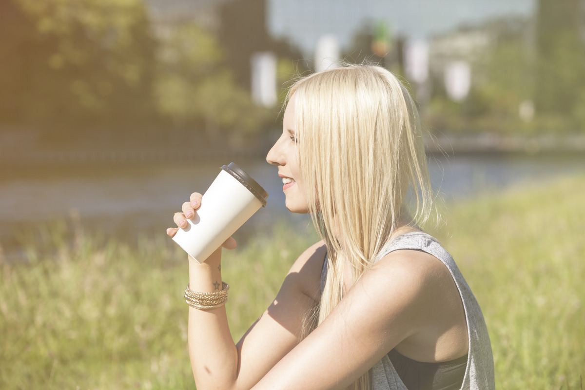 A woman drinks coffee while sitting on the grass.
