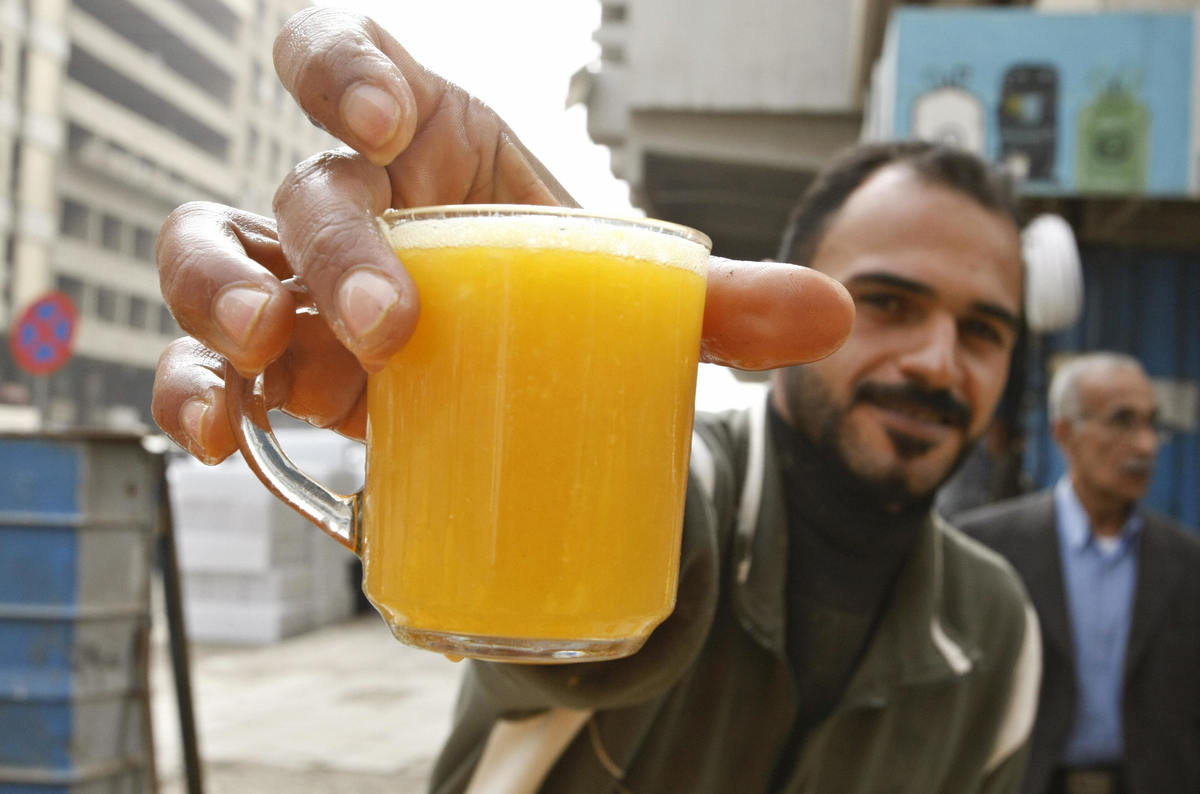 A vendor holds out a glass of fresh orange juice.