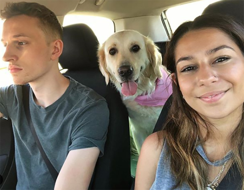 Lola looks at the camera while Amber takes a selfie and Alex drives.