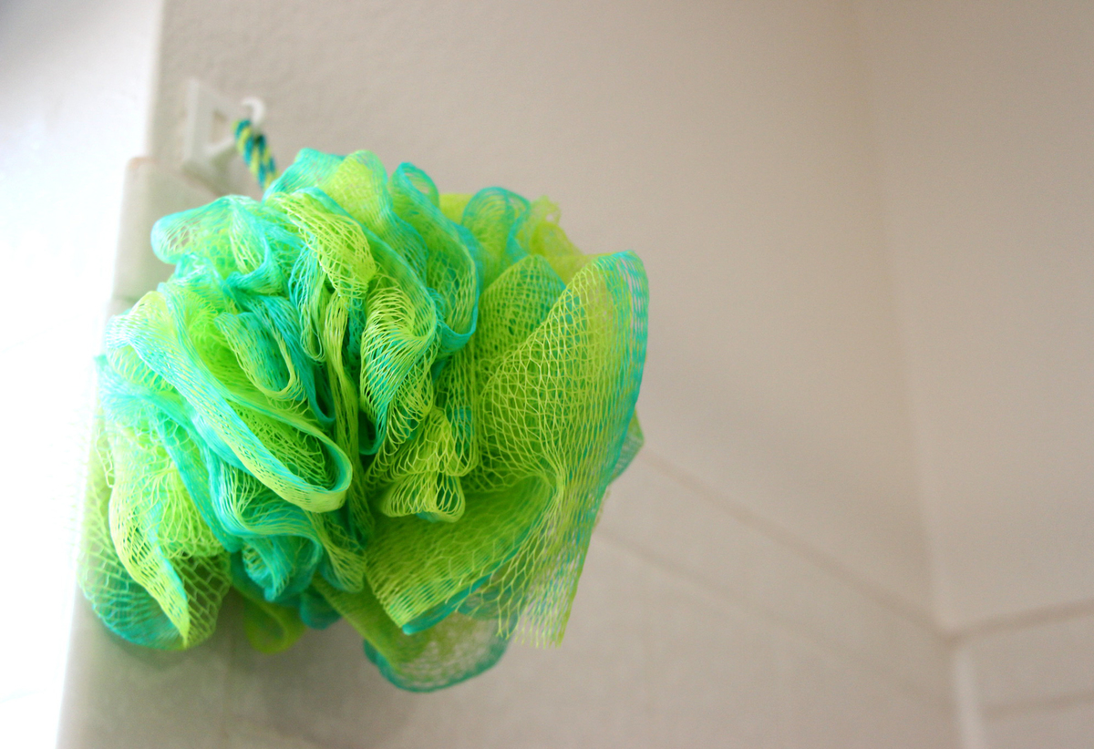 A green loofah hands on a hook in the shower.