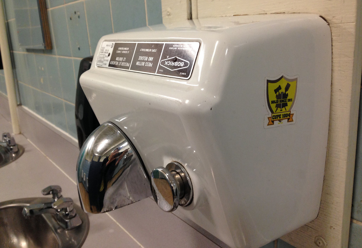 A hot-air hand dryer is seen in a public restroom.
