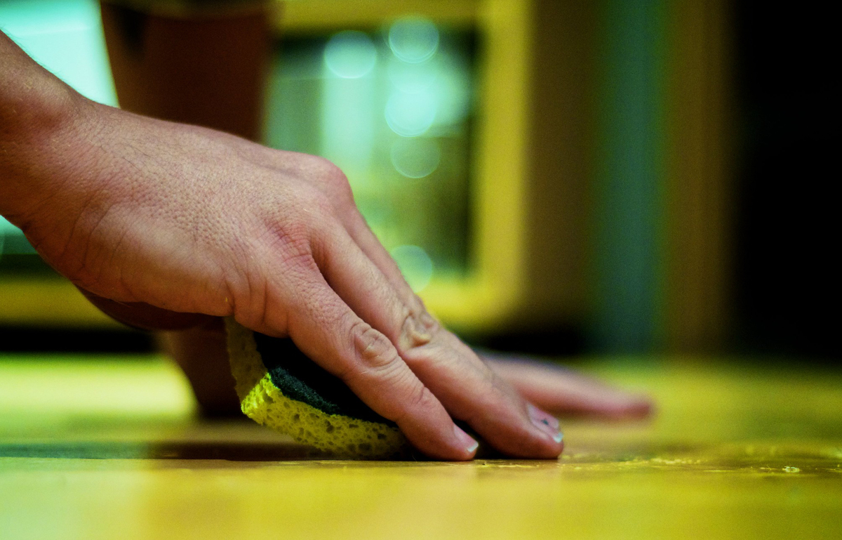 A person wipes a sponge across a yellow table.