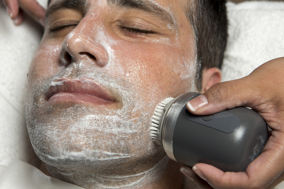 A salon owner uses an exfoliating scrub on a man's face.