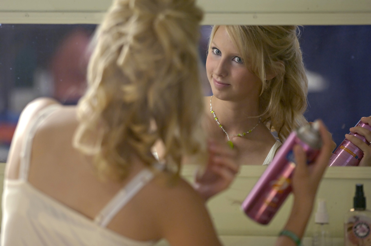 A model sprays her hair while looking in the mirror.
