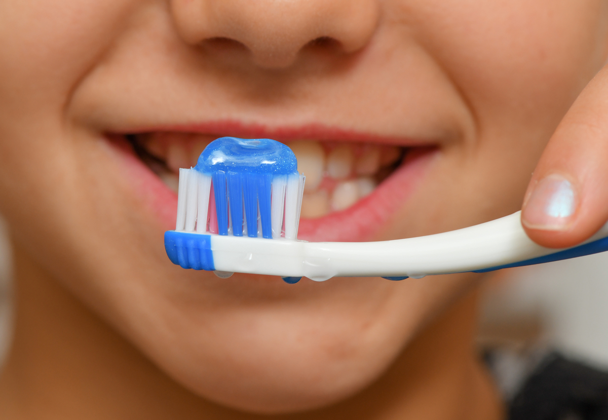 A child holds a toothbrush with toothpsate on it near her mouth.