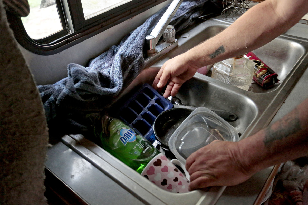 A person sorts through dirty dishes in the sink.