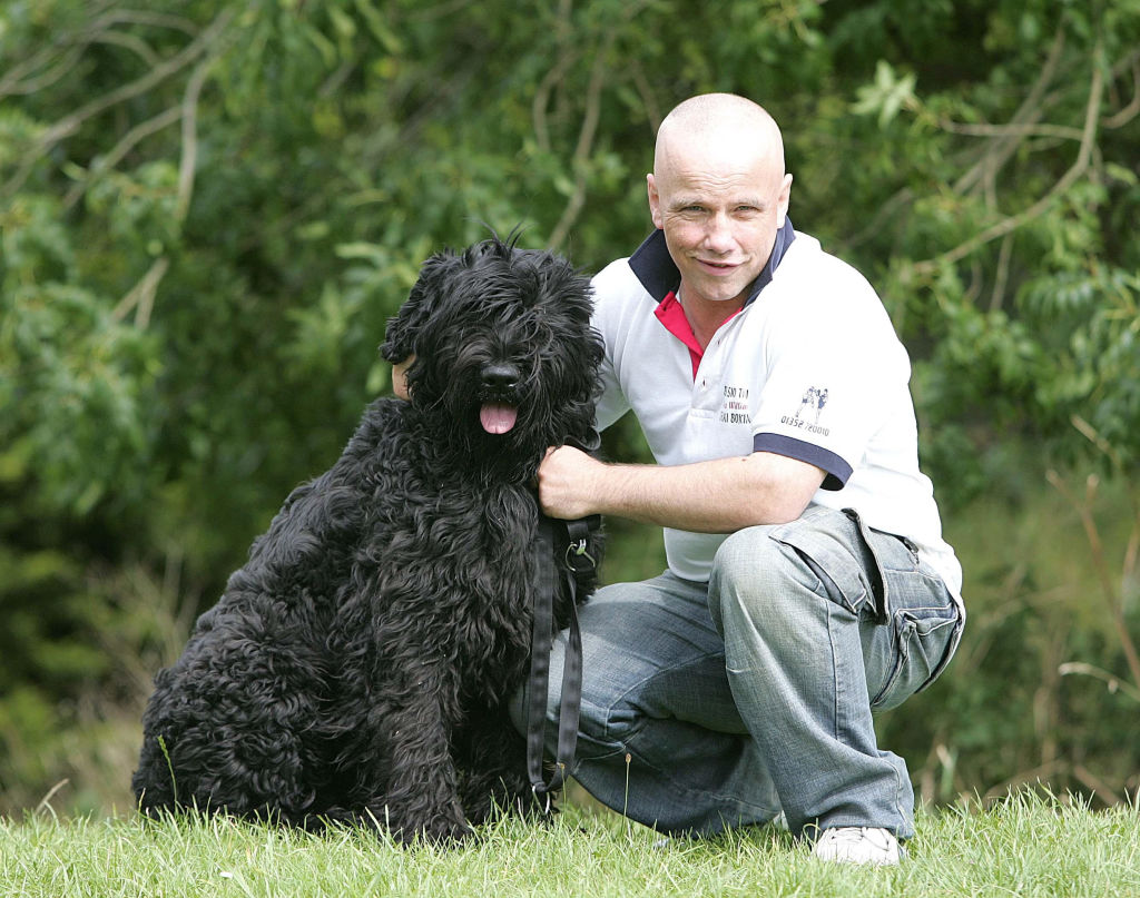 A Black Russian Terrier sits in the grass next to its owner.
