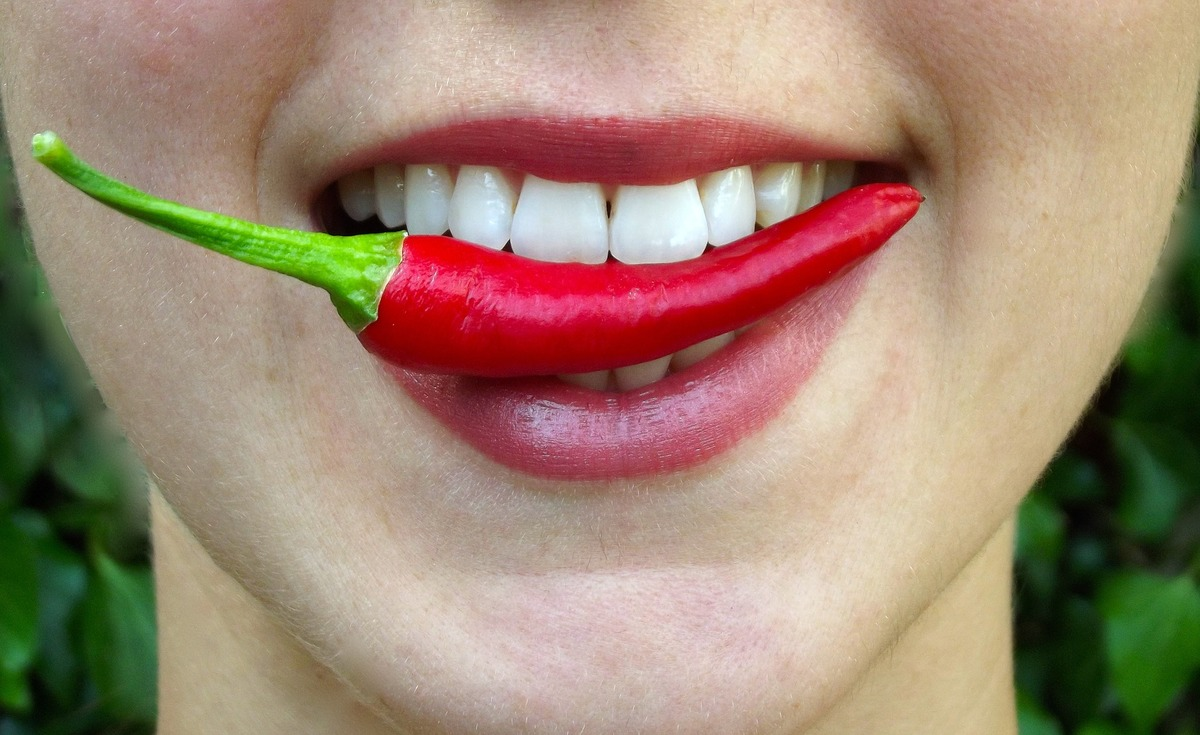 A woman holds a chili pepper between her teeth.