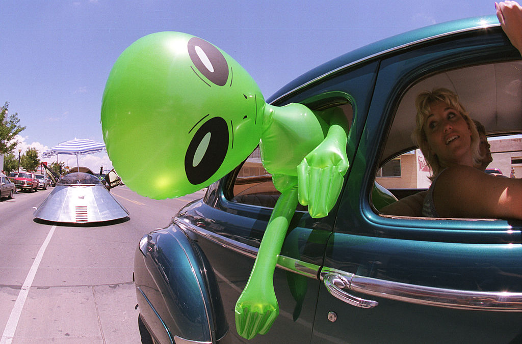 a woman driving with an inflatable alien in roswell, new mexico