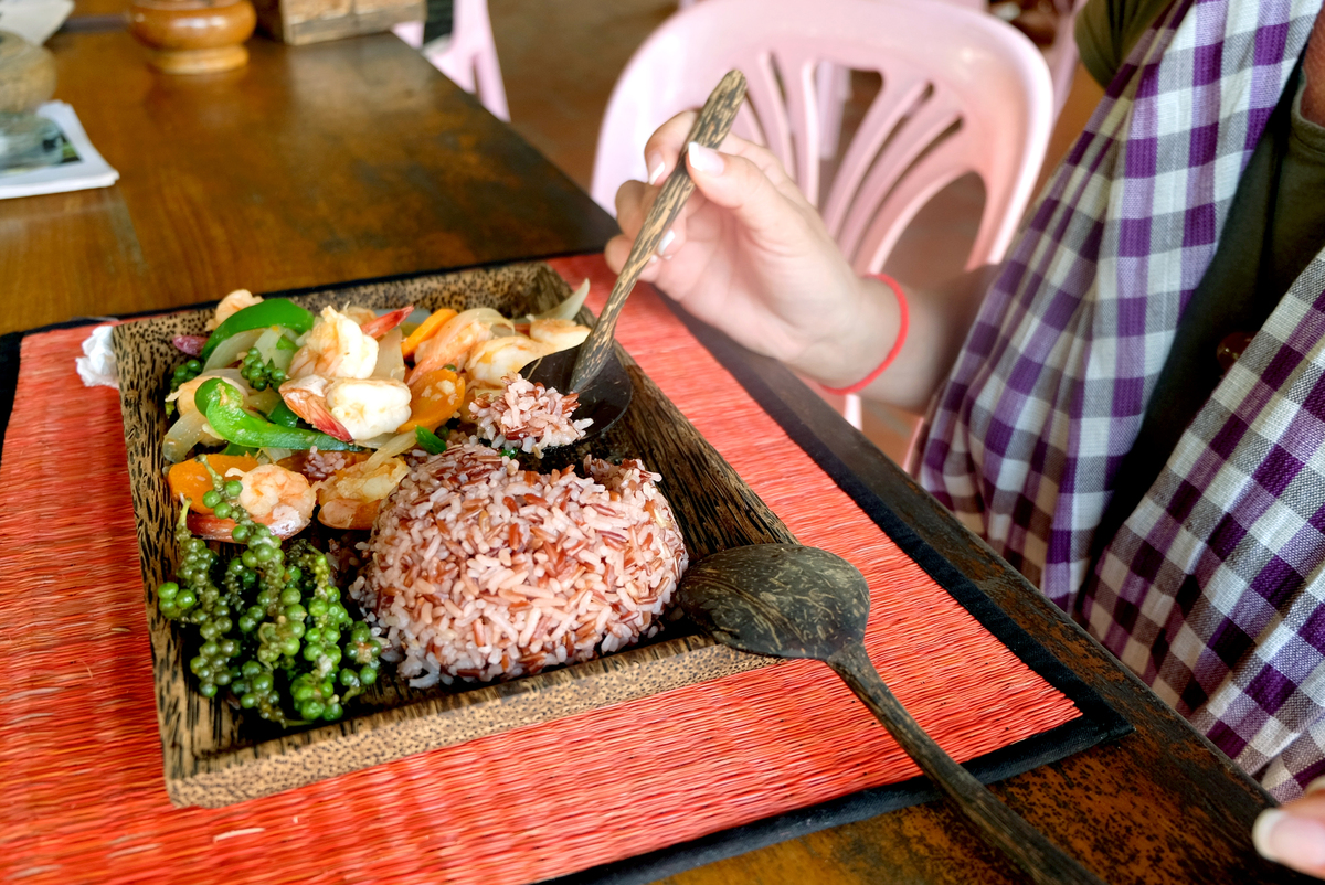 A customer eats brown rice with a spoon at a seafood restaurant.