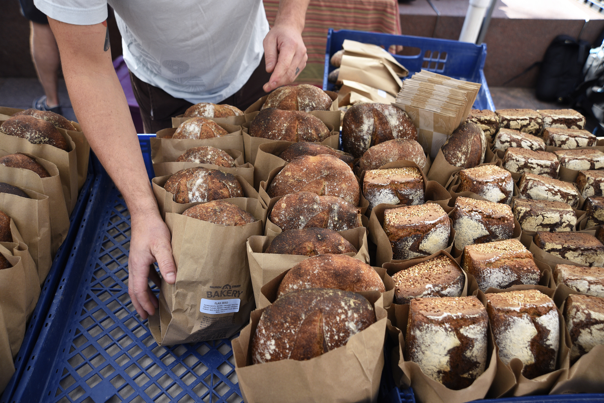 A bakery worker arranges a display of artisan bread.