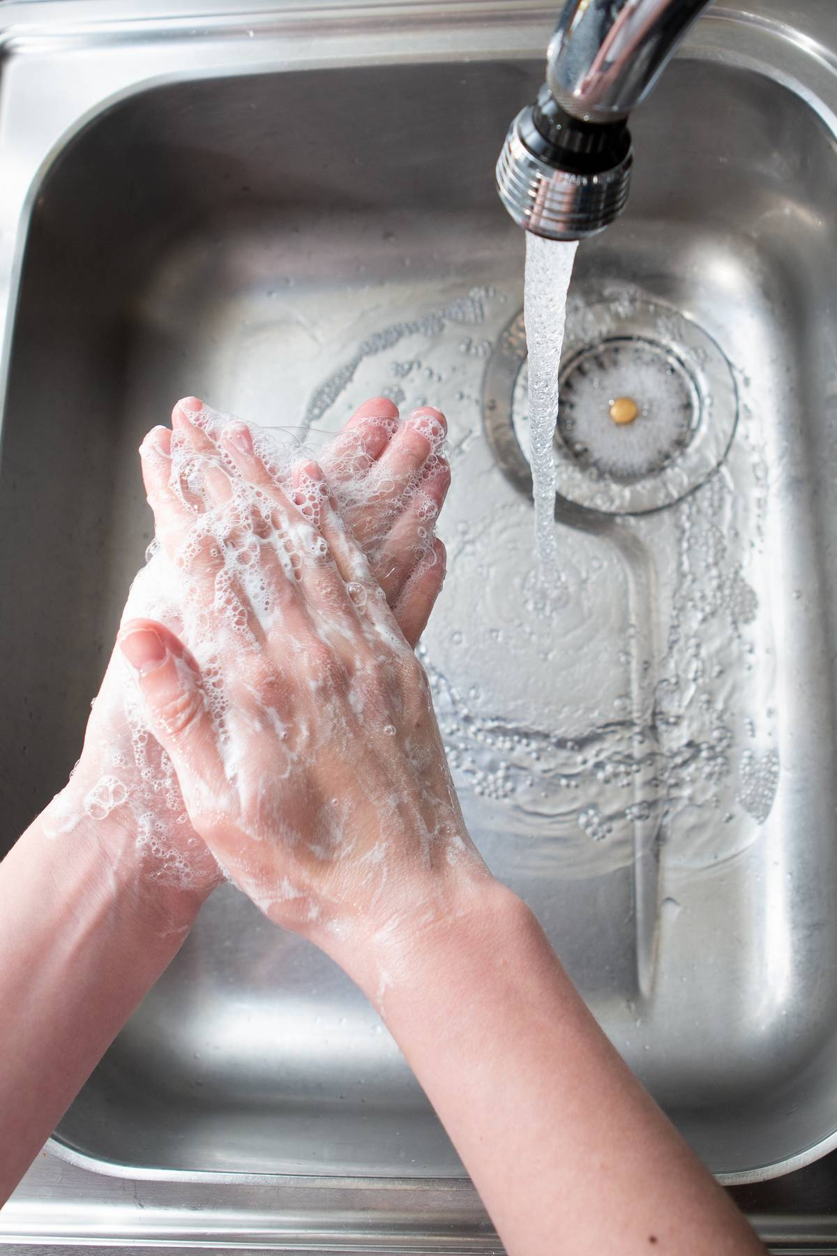 A person washes her hands in the sink.