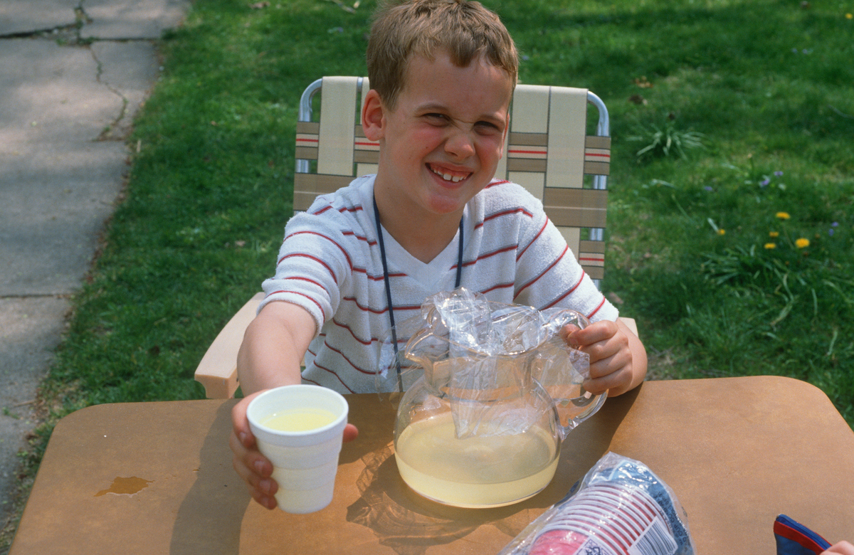 A young boy sells lemonade at an outdoor table in Chicago.