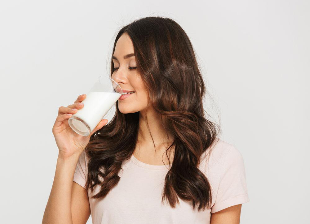 A woman drinks a glass of milk.