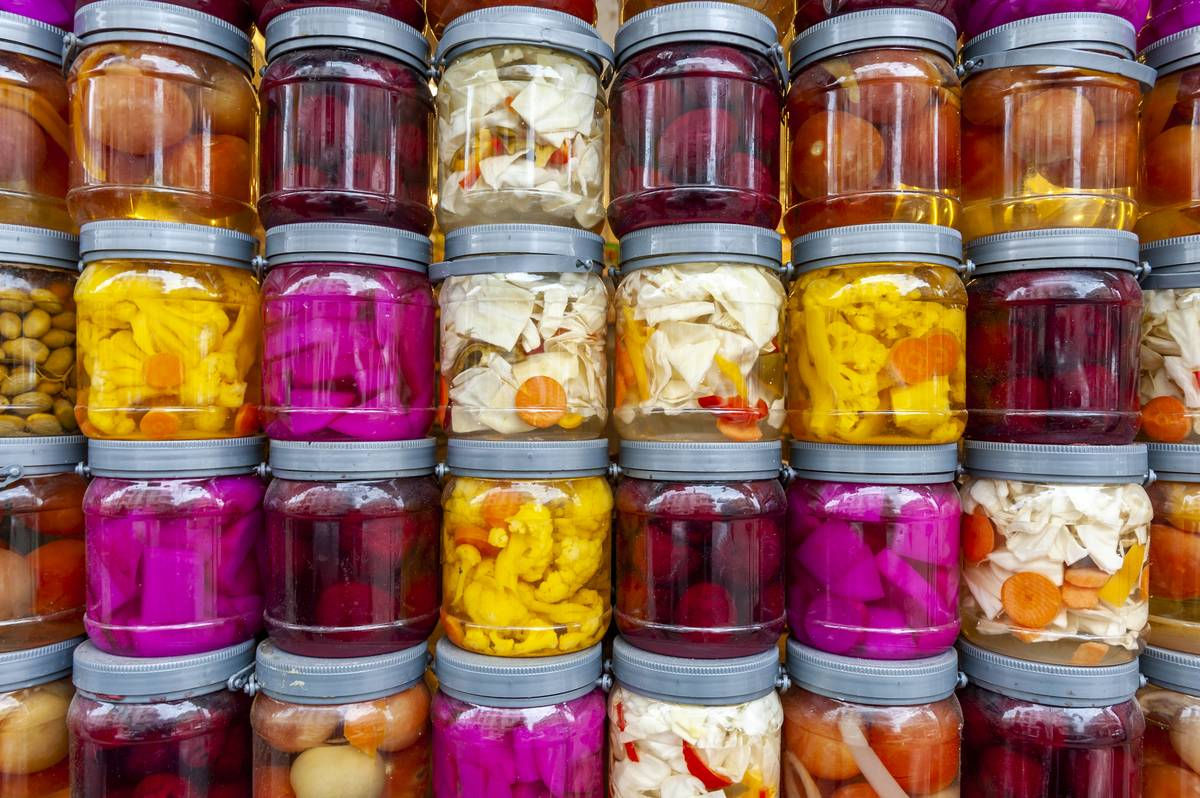 Jars of pickled fruits and vegetables are stacked on top of each other.