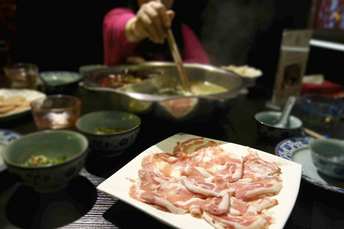 Customers eat mutton in a hotpot in China.