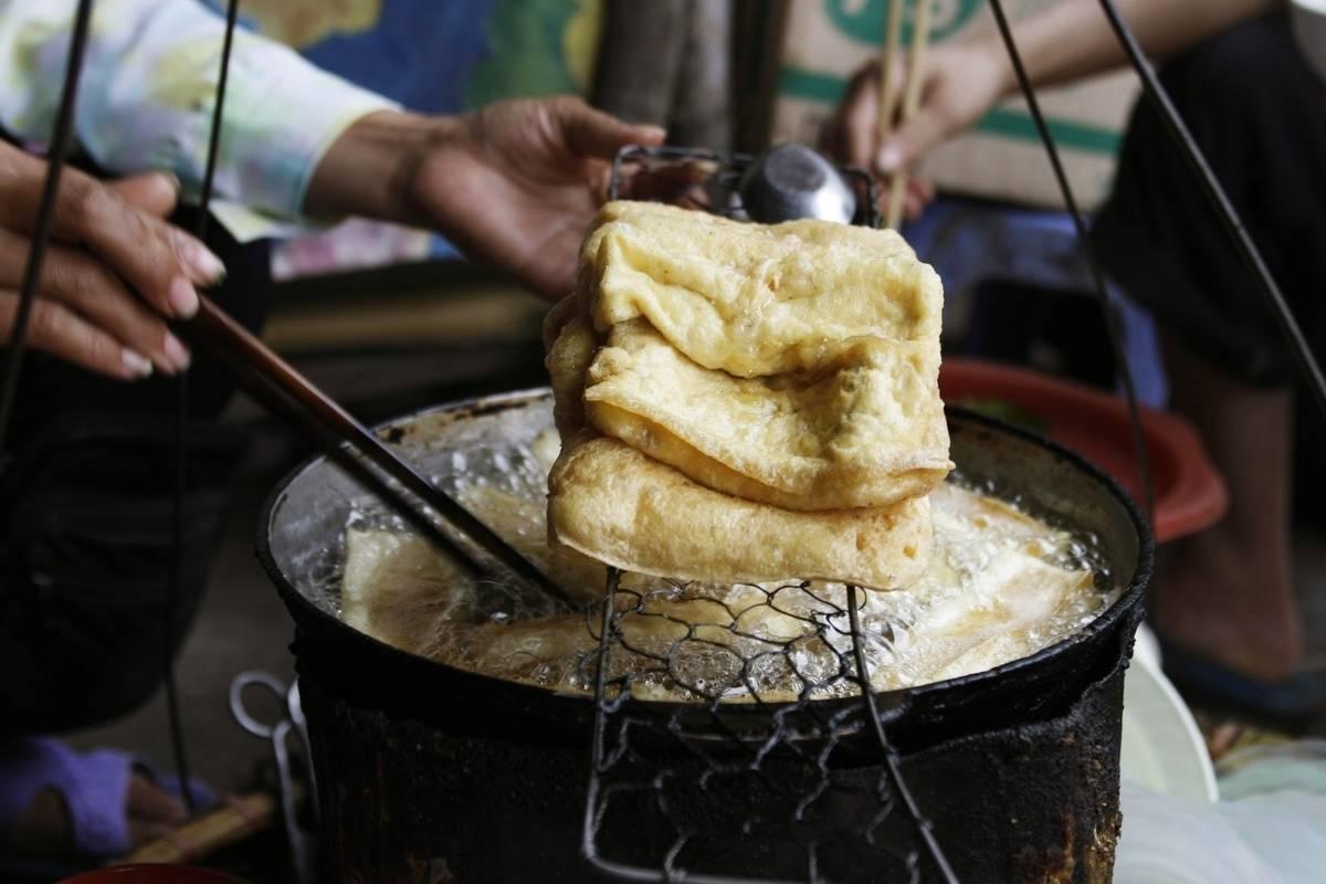 A street vendor fries tofu in Vietnam.