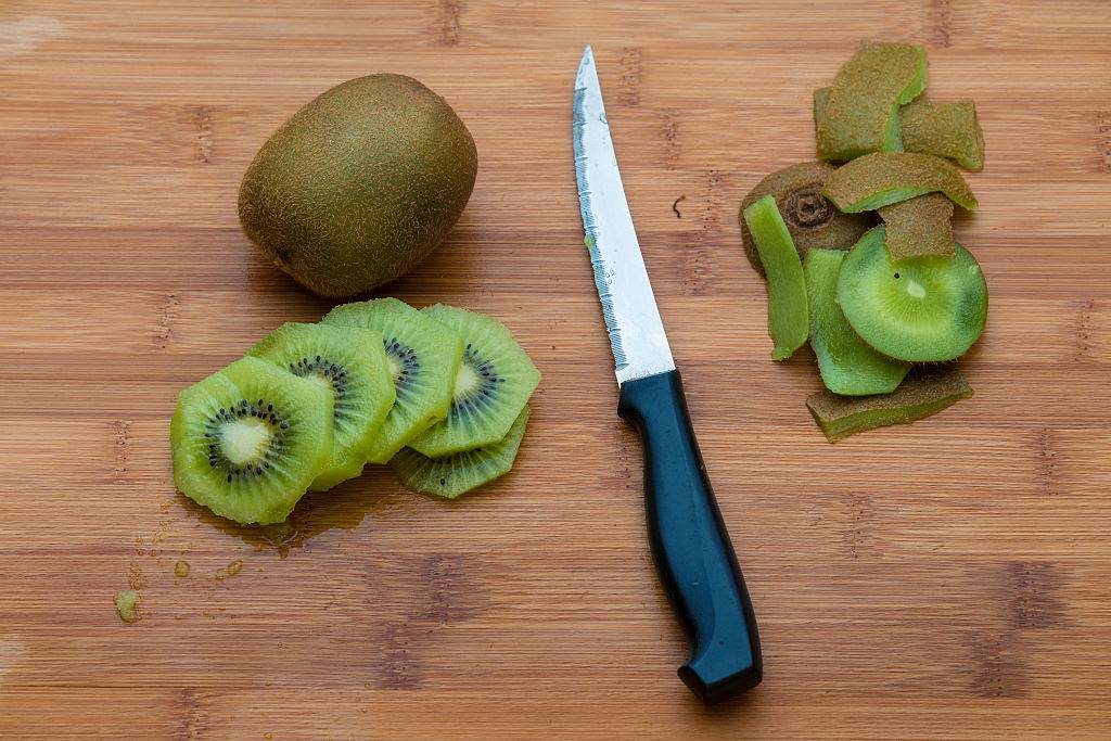 Kiwifruit on a wooden chopping board with a knife
