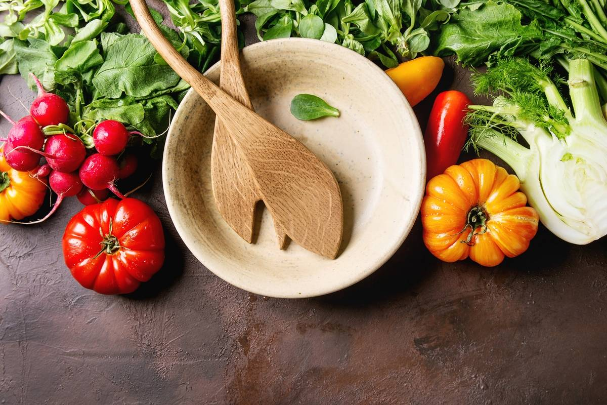 A variety of vegetables surround a bowl with wooden salad serving spoons.