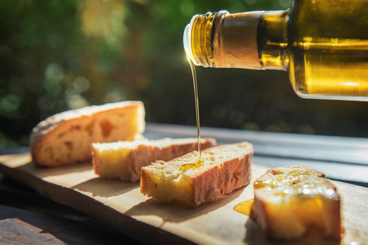 A person pours olive oil onto a piece of bread.