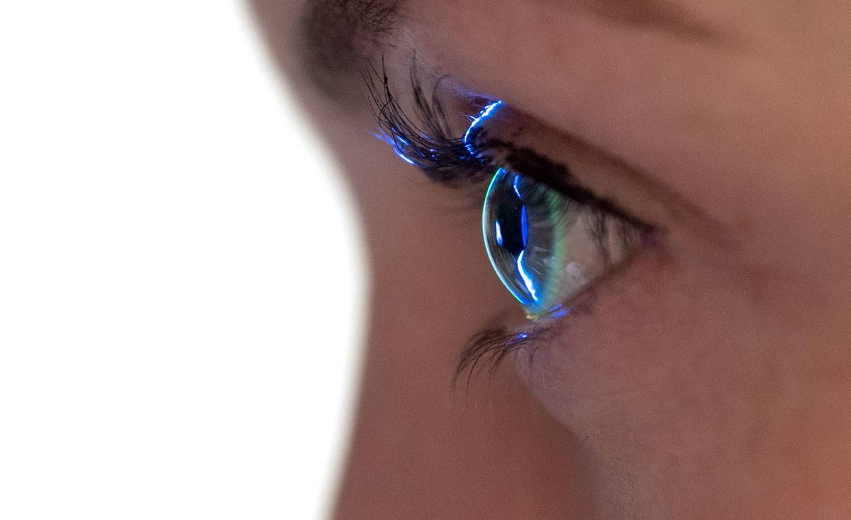 Light shines on a woman's eye during a vision exam.