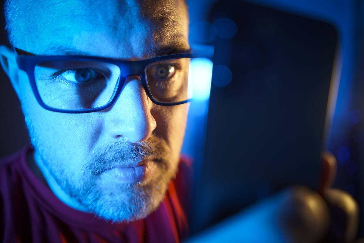 A man wearing glasses looks intensely at his phone.