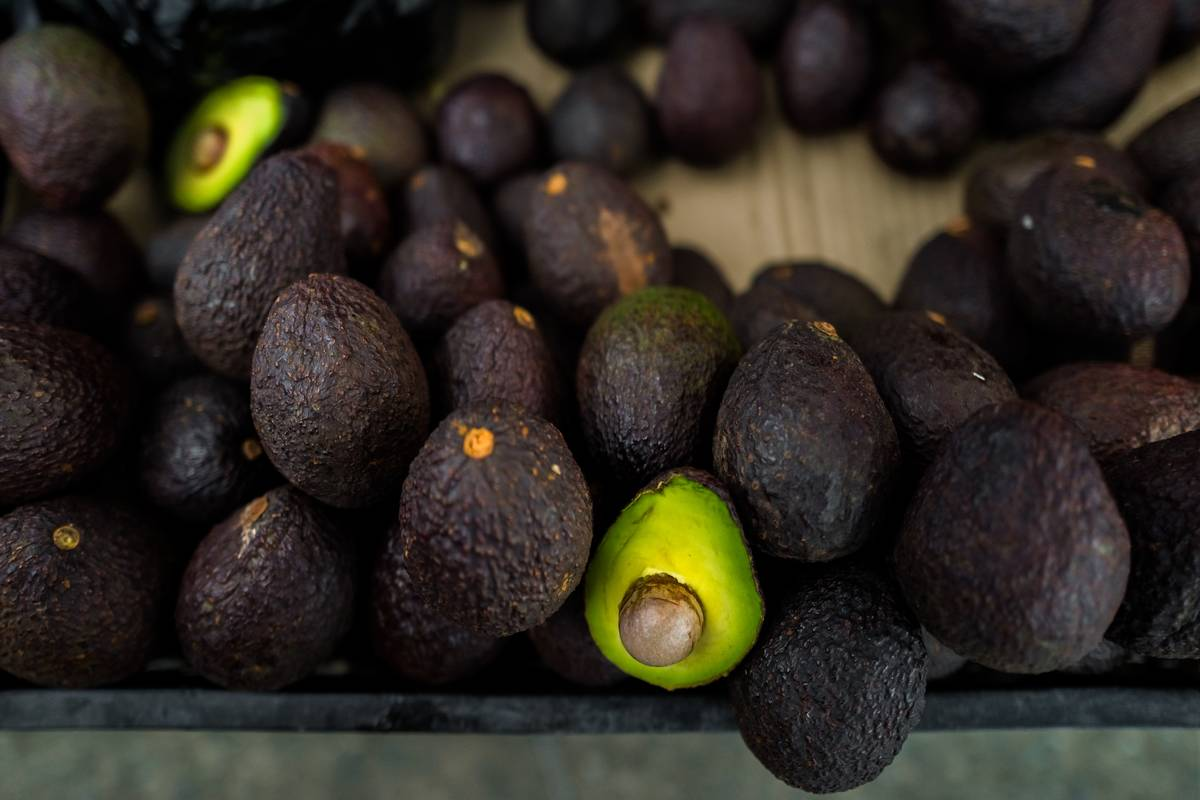 Ripe avocados sit in a pile, and one is cute in half.