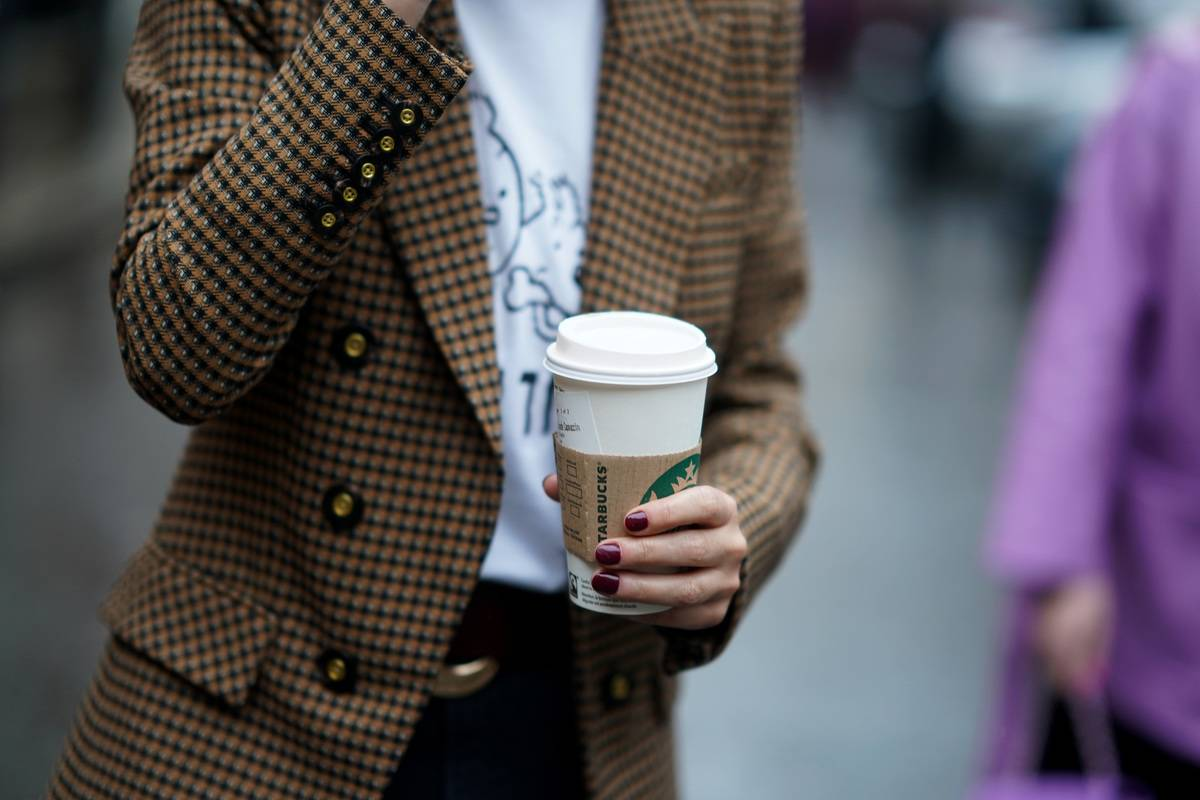 A woman holds a Starbucks coffee as she walks down the street.