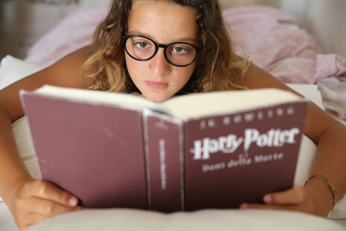 A girl reads Harry Potter in bed.