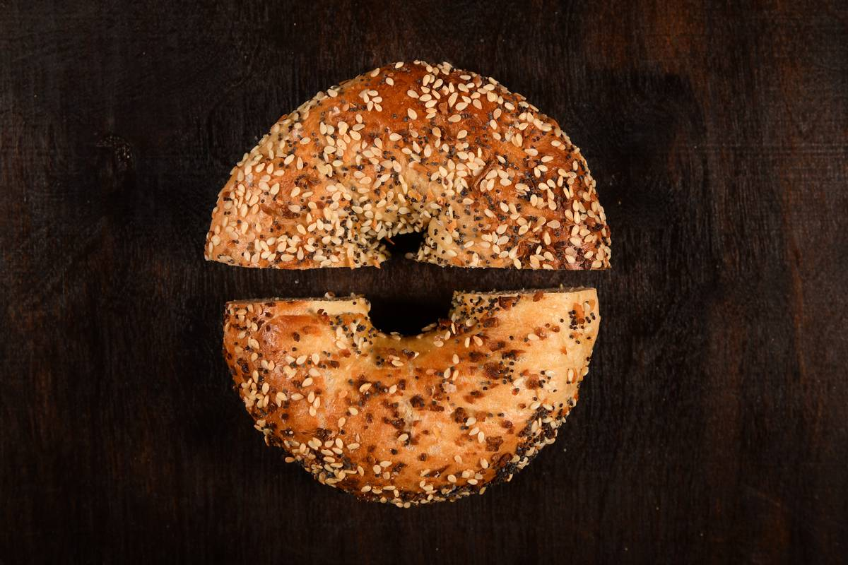 An everything bagel is cut in half.