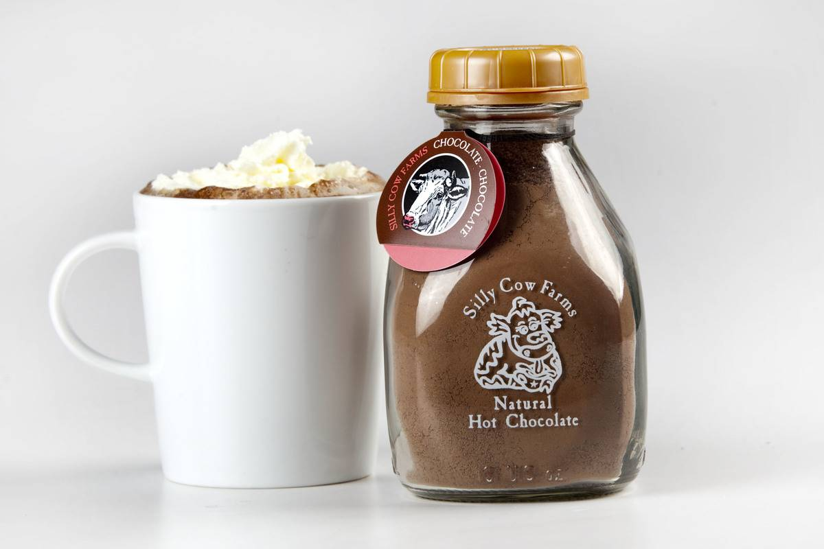 A cup of hot chocolate sits next to the chocolate mixture.