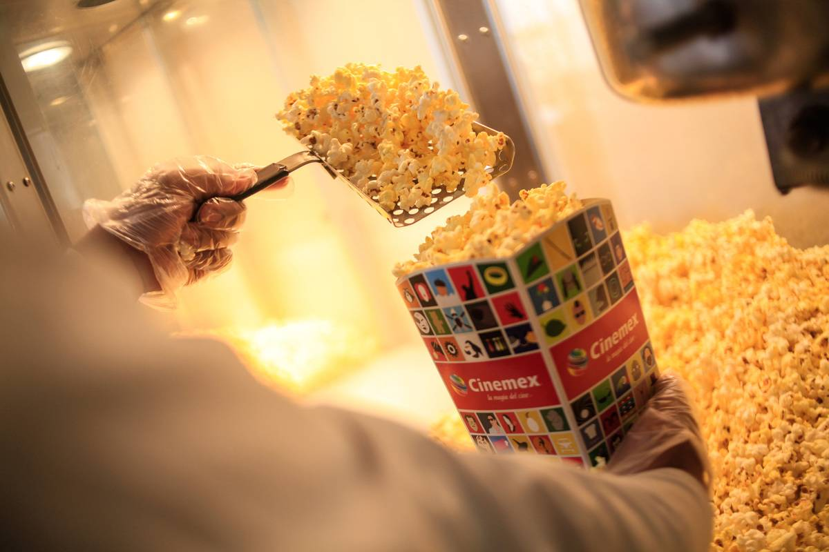 A movie theater employee dishes popcorn into a bag.