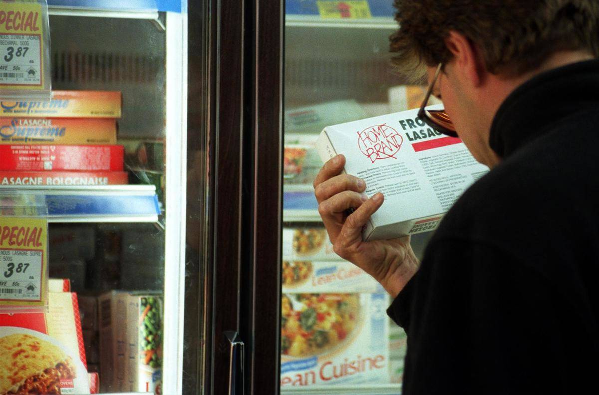 A man reads the nutrition label on a frozen dinner package.