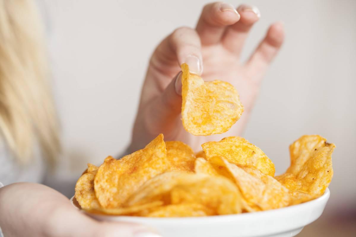 A woman eats potato chips.